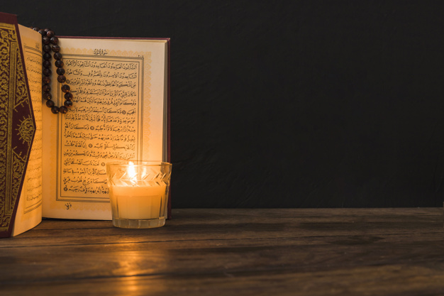 glass-with-candle-near-opened-quran_23-2147868989.jpg